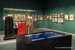 Ein Raum verziert mit Bildern an den Wänden, einem interaktiven Display und einer großen Steckvitrine von Frank mit schwarzem Bodenrahmen, welche prachtvolle, fernöstliche Gewänder aufbewahrt.