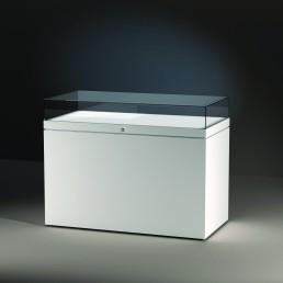 Frank bietet mit der Excel Line auch konventionell gefertige Glasvitrinen. Hier wird eine Tischvitrine mit offenem, weißem Sockel/Basis gezeigt.